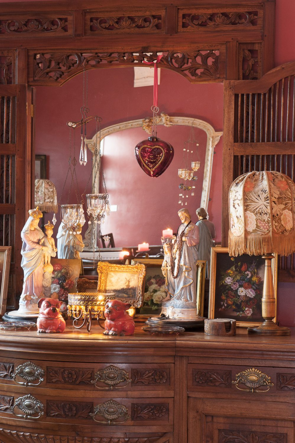 In the dining room the surface of an ornate cabinet is filled with miniature paintings in gilded frames and objects from the couple's travels