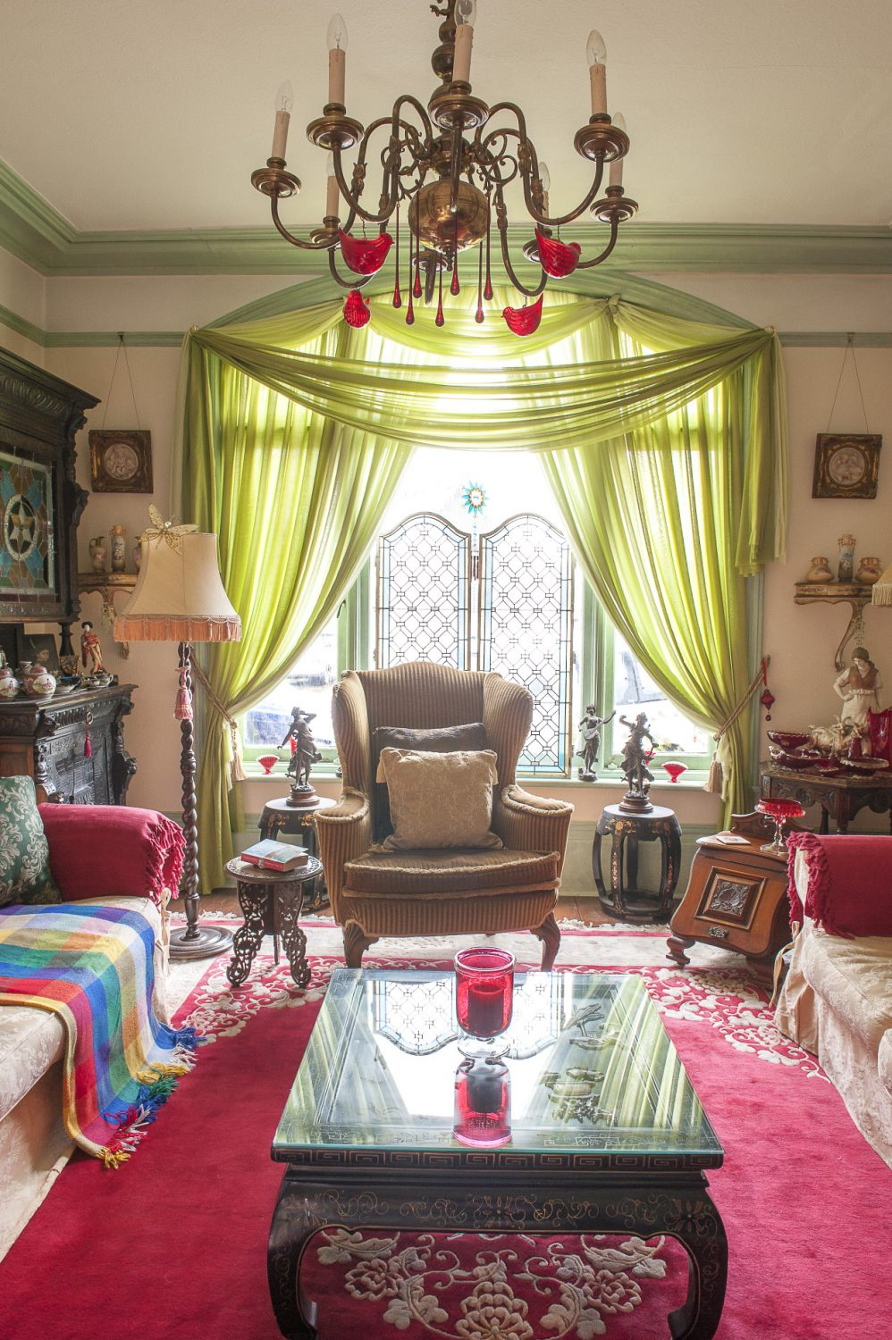 A window is generously swathed with metres of rich green fabric in the more formal of the two drawing rooms