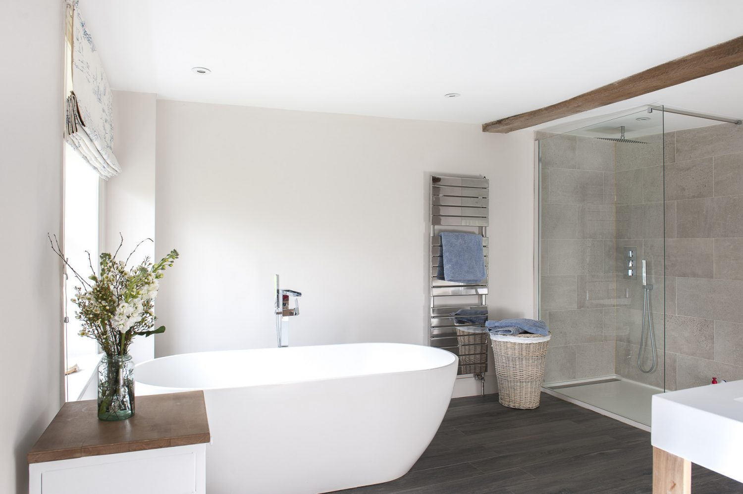 The contemporary en suite bathroom with modern standalone bath, spacious walk-in shower and limed oak flooring is a far cry from what the couple discovered when they bought the house which 'wasn't a wreck but needed a lot of updating'. Bathers get an uninterrupted view over the front garden