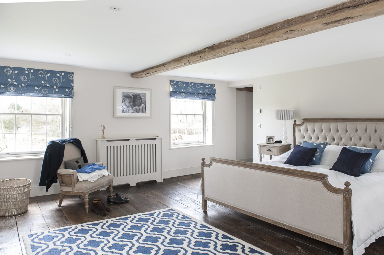 The master bedroom retains its original, wide oak floorboards. Waxed rather than stained, they provide the perfect backdrop for this pretty patterned rug and classic bedroom furniture including a bed by Feather & Black