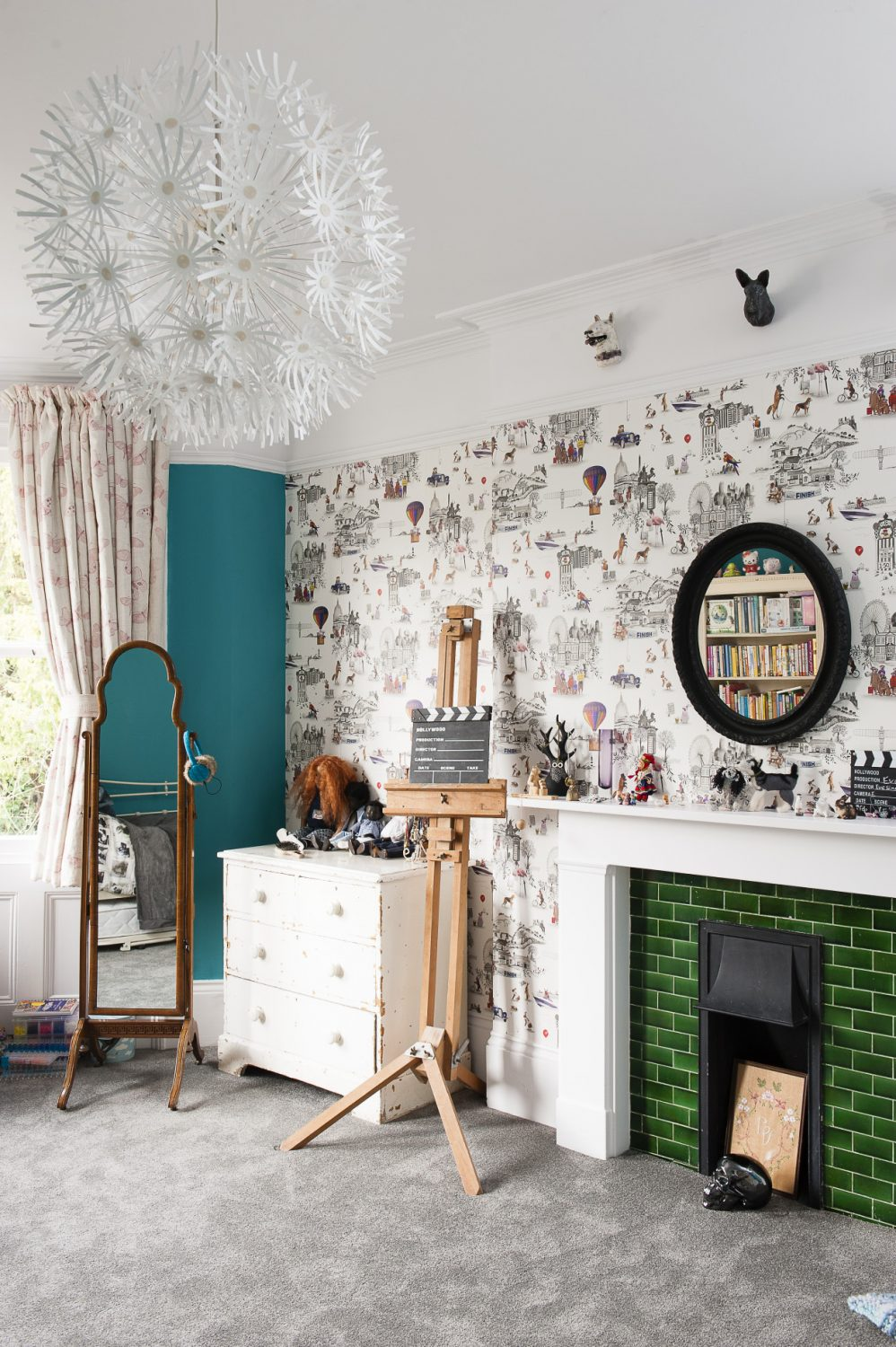 Catherine's daughter's room features a wall and chimney breast papered in lighthearted Meerkat wallpaper