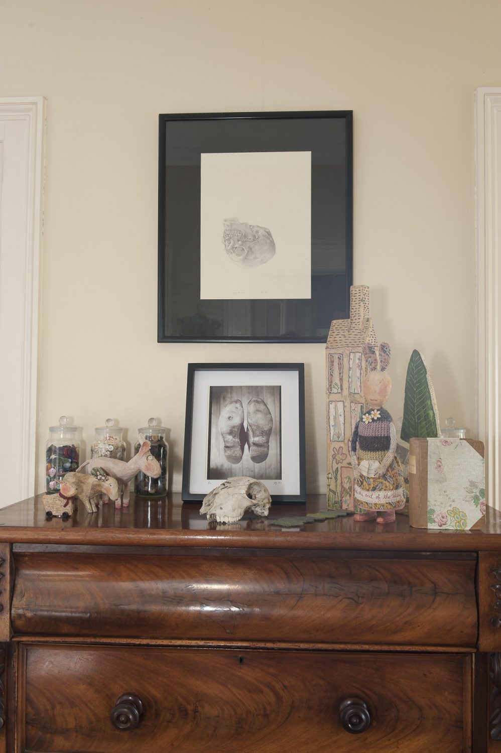 A rabbit by paper sculptor Julie Arkell nestles amongst a collection of artworks on the landing including a photo and drawing by Jonathan Wright