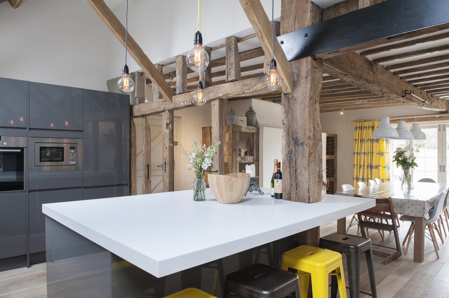 The kitchen was originally three rooms. Now open plan, an Aga and large kitchen table occupy one end of the room while a sleek modern kitchen by Howdens occupies the other. Overhead lighting comes from rooflight windows during the day and funky filament lights at night