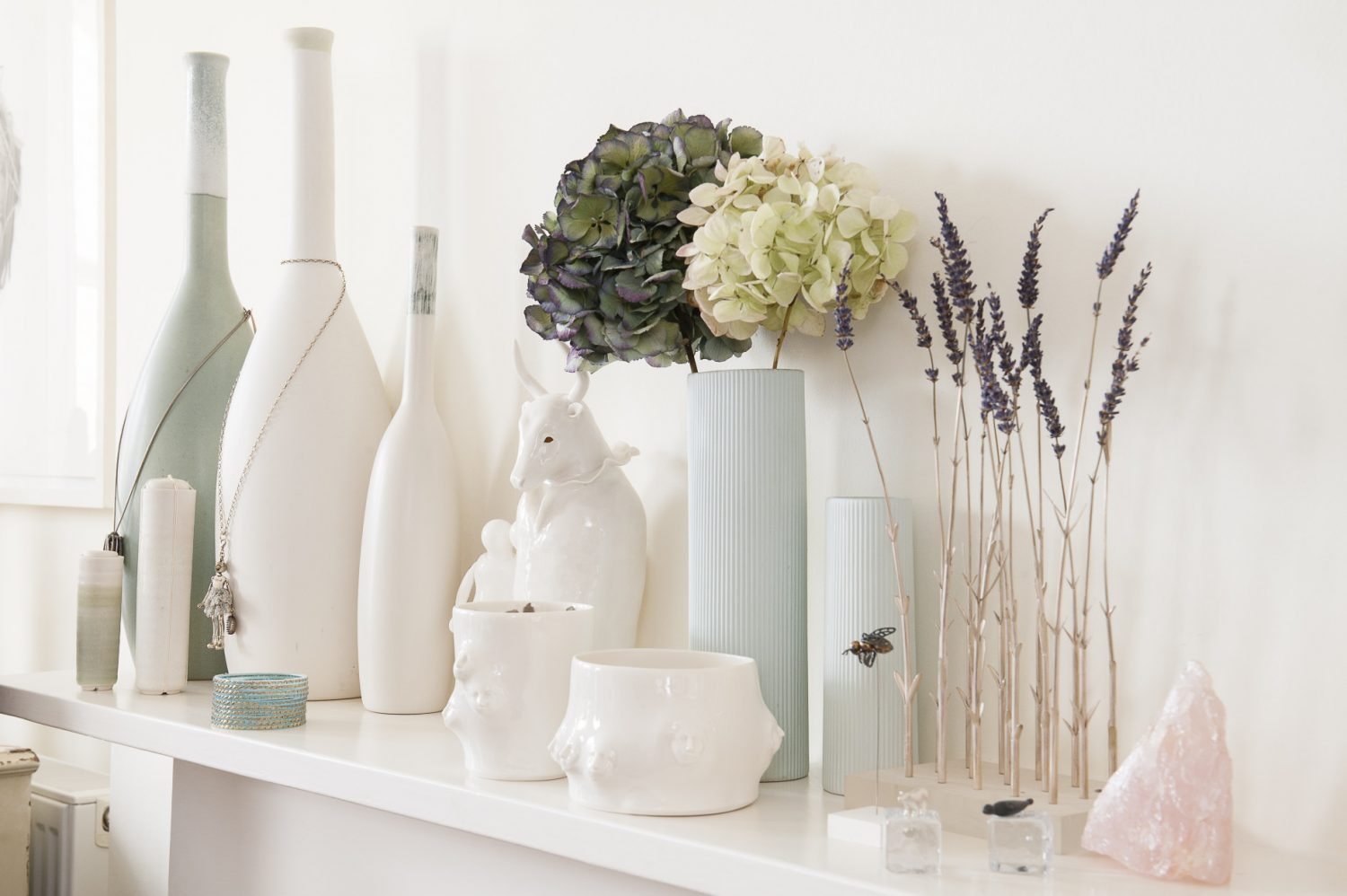 Rose quartz and lavender sits alongside ceramics on the mantlepiece
