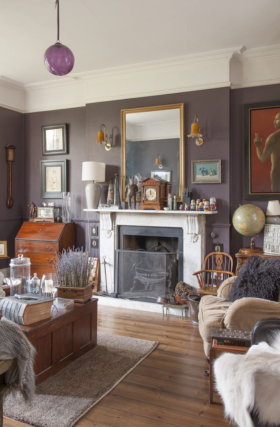 The more formal of the house's two drawing rooms is painted a deep, rich aubergine, creating the perfect background to showcase the couple's collection of artworks