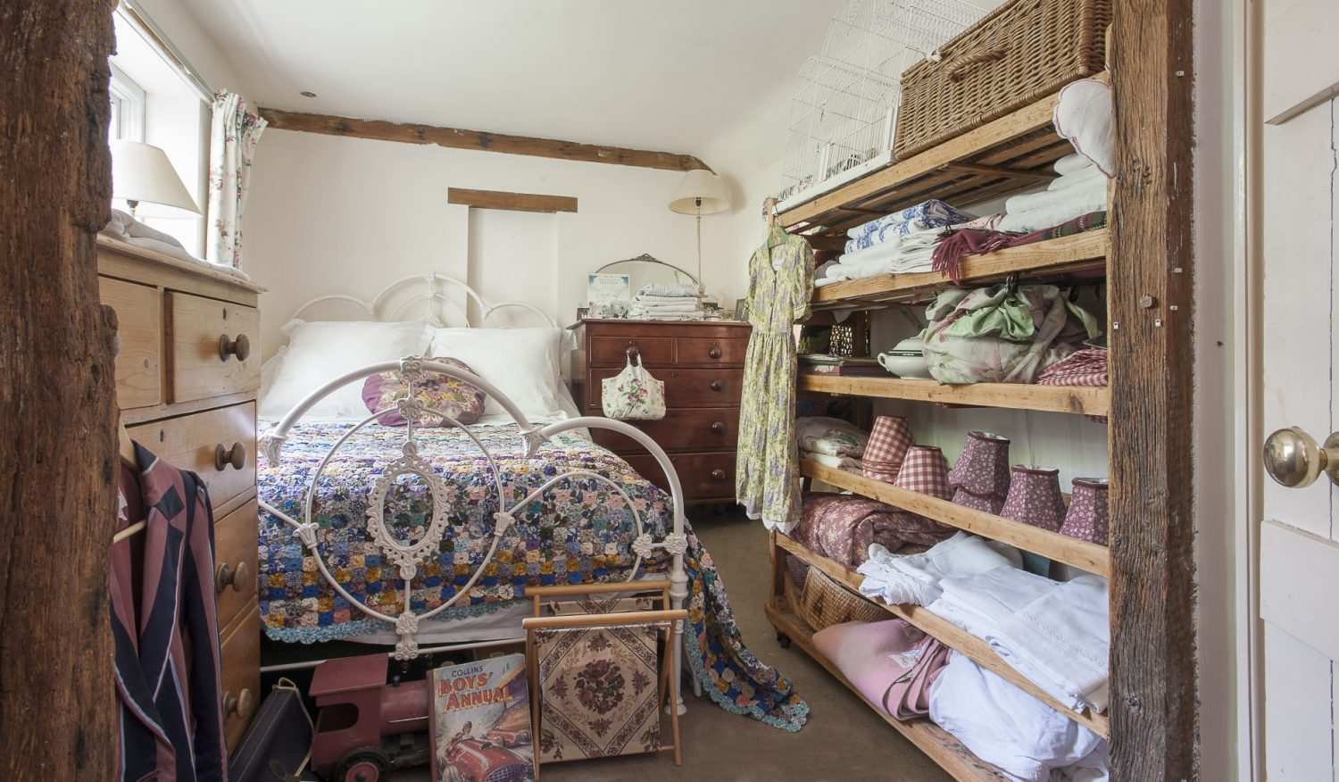 Shelves in the guest bedroom are home to stacks of crisp French linens and a brightly coloured vintage yoyo quilt dresses the painted metal bed