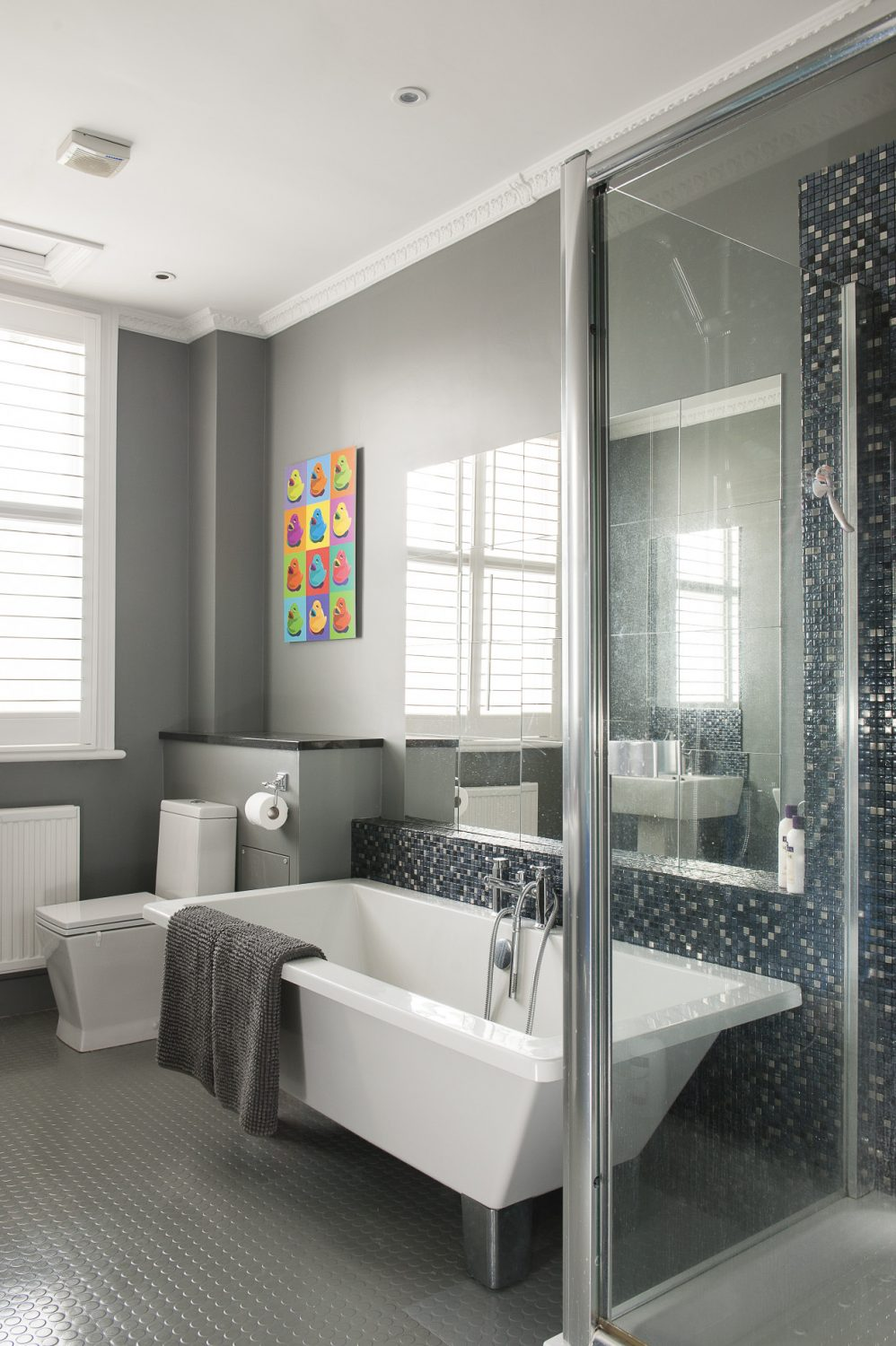 Adhering to a colour palette of cool greys in the family bathroom, Catherine has chosen rubber flooring and striking pearlised mosaic tiles