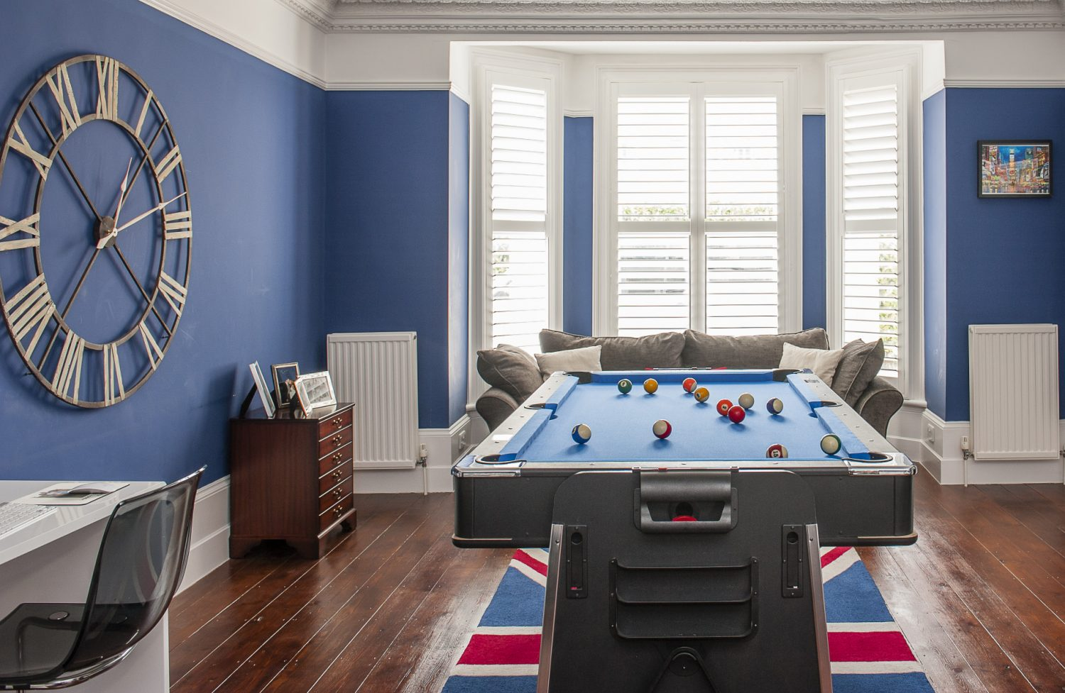 What will eventually become a formal dining room is currently the ultimate gaming room gathered around a pool table that flips over for air hockey in the centre