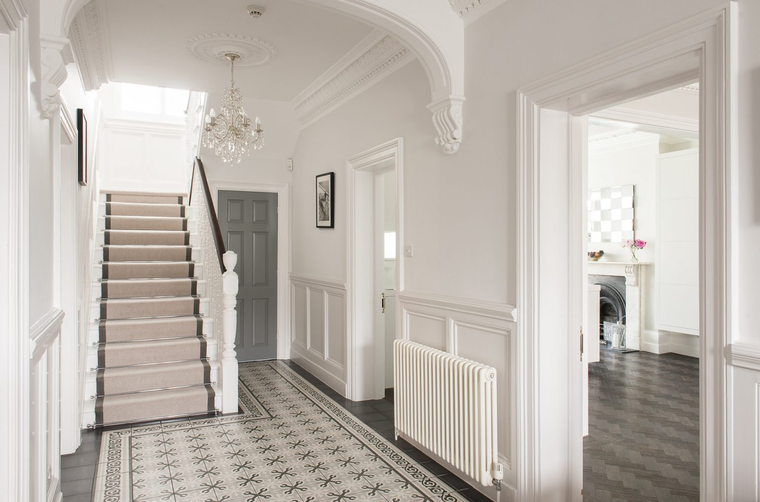 Beneath a sparkling chandelier, the impressive entrance hall features a floor tiled in Fired Earth 'Patisserie' tiles