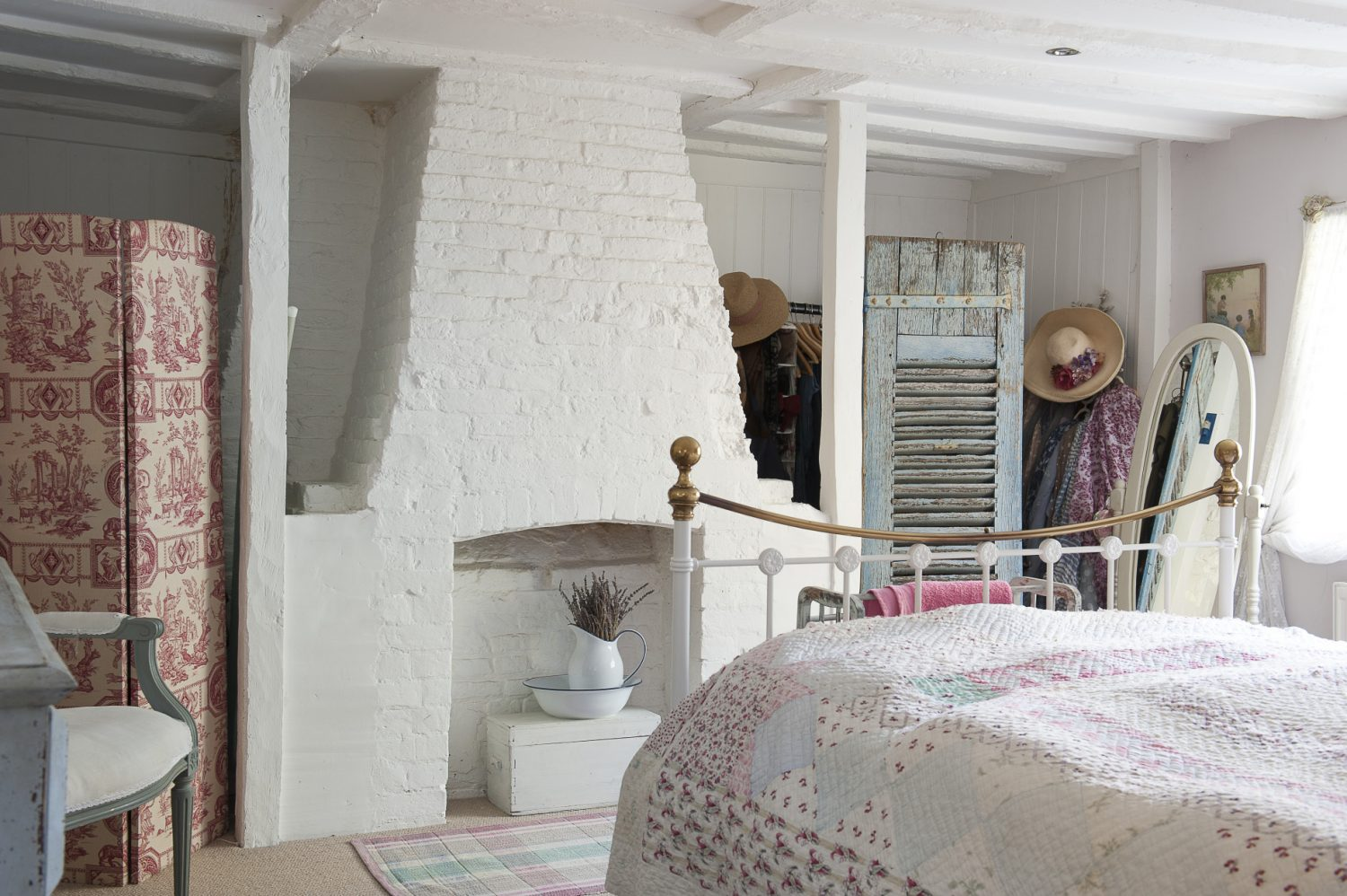 The bricks of a disused fireplace in an upstairs bedroom have been painted white to reflect the light – and avoid the gloominess associated with low, beamed ceilings. A Victorian-style bed is draped with a lovely handmade spread from Love Lane Vintage