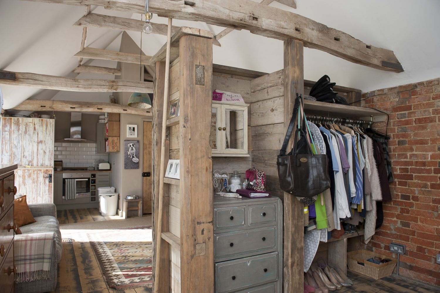 One of the outhouses at Brick House Farm is home to the couple's daughter. The space was designed by Rob in a 'more masculine style', according to Caroline, or 'modern rustic', and incorporates salvaged wood from around the farm. A kitchen corner, sleeping area and living room are cleverly combined in an open-plan arrangement