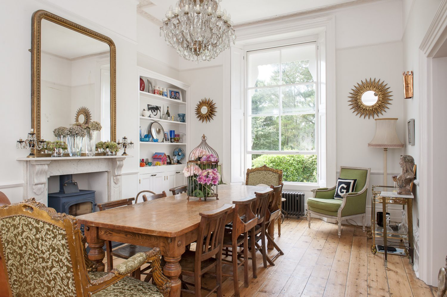 In the dining room, Louise has opted for a big oak runway of a refectory table surrounded by an eclectic collection of chapel chairs. Over the table is another impressive chandelier and over the white marble fireplace is set a large Louis Philippe mirror