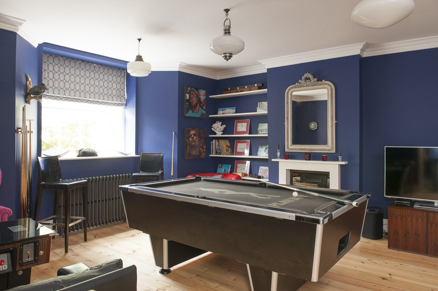The boys' blue playroom is dominated by a full-size pool table with a supporting cast of an original Space Invaders console