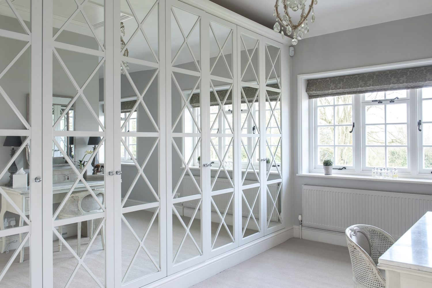 A wall of bespoke wardrobes with mirrored and lattice-work doors in the dressing room was beautifully crafted by the couple's carpenter, Robert and fits perfectly with the property's 20th century, Arts & Crafts aesthetic. Hiding any clutter, they are also eminently functional too