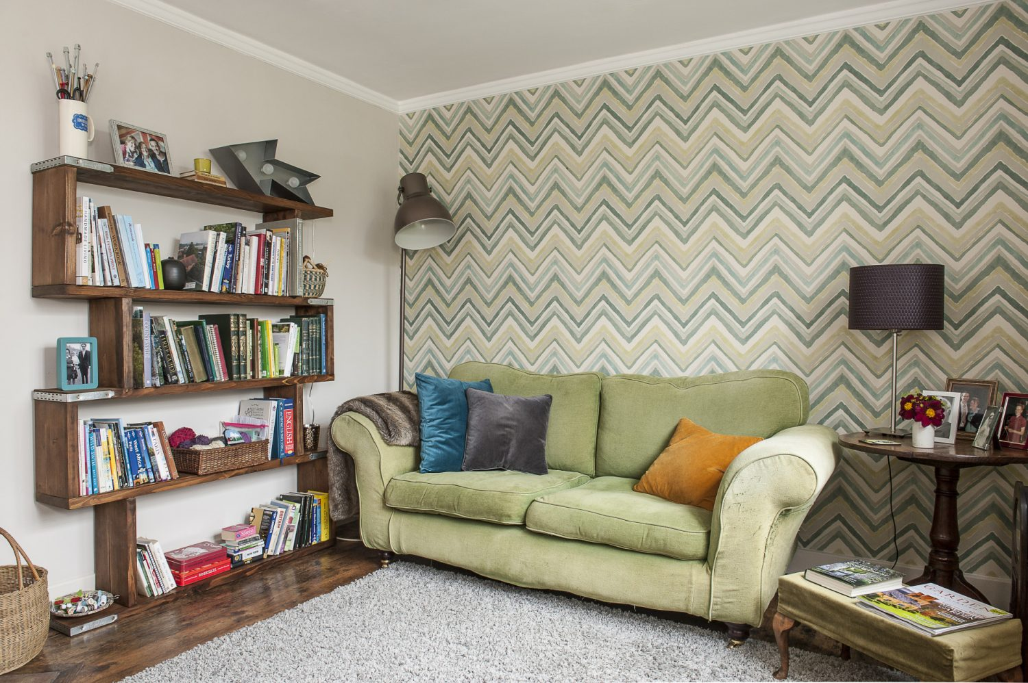 Colour-blocking with cushions keeps things simple, in front of the vibrant zig-zag wallpaper. The bookshelf is made from scaffolding boards and was inspired by a version that Claire saw in a high street store.