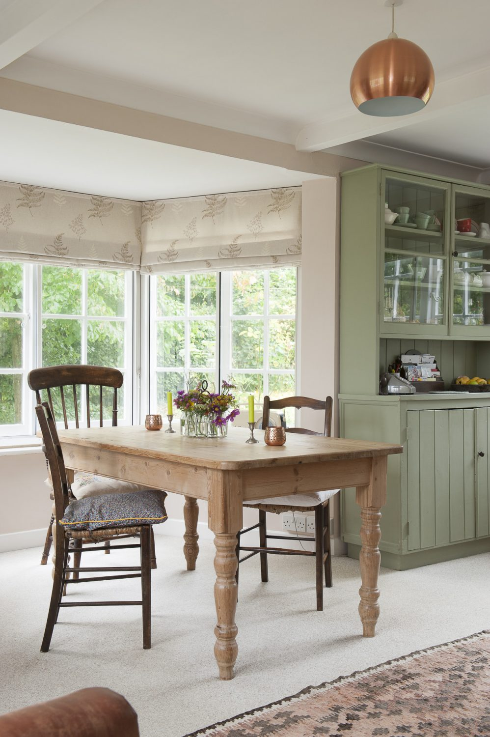 Mismatched chairs complement the informality of the rustic table
