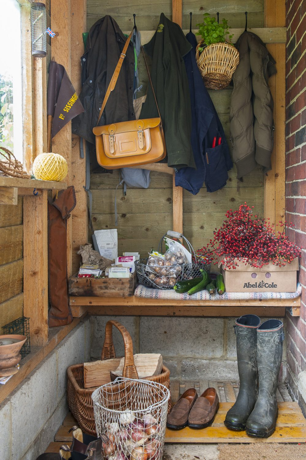 One look in the porch, and it's clear this is the home of a gardener; bulbs, seed packets, vegetables and herbs – and the essential pair of wellies – stand at the ready. A gift of ornamental rose hips from a friend lie ready for use in the house as decoration, and logs are stacked to take in for the fire