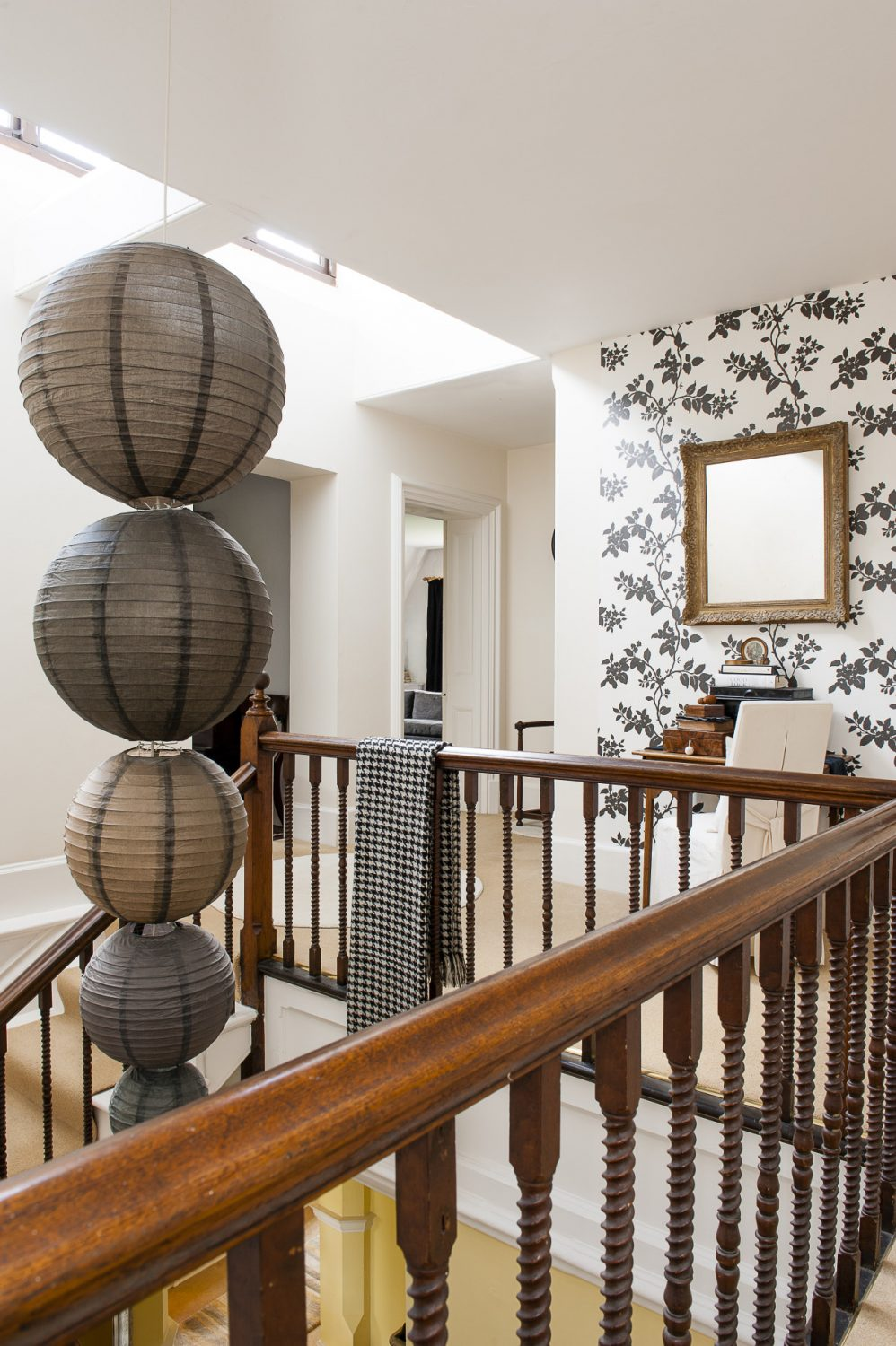 A lovely original staircase hung with a bespoke string of paper lanterns leads to the top floor, part of which was probably the original family's children's bedrooms and perhaps the nursery