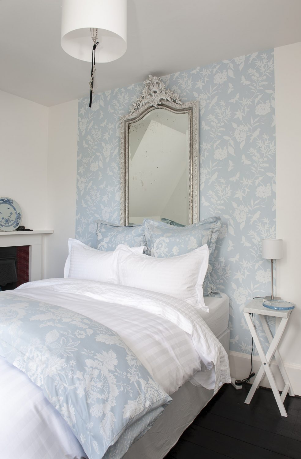 Above the bed is a panel of pretty pale blue wallpaper and a patinated antique French mirror and, standing by, is a pair of mother-of-pearl inlaid chairs reupholstered in blue. Dan has painted the floor in black gloss