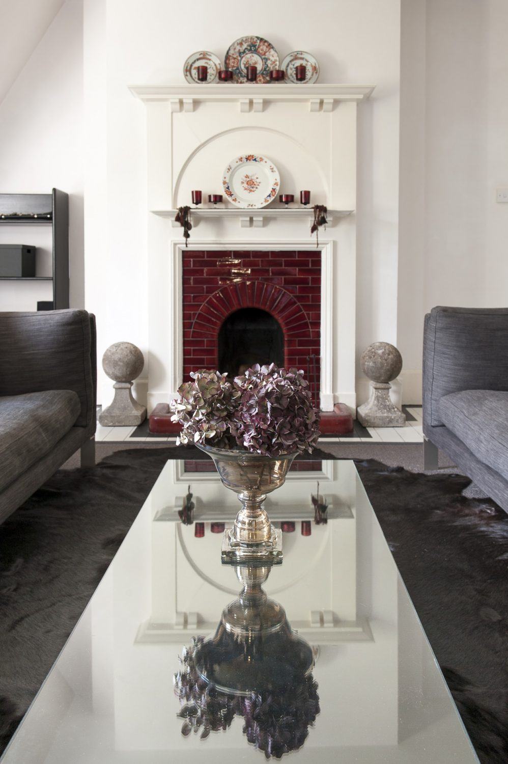 Two huge grey velvet Habitat sofas recline on black cow hides facing each other across a long glass table. In the widow hang matching grey velvet curtains and the whole scheme is perfectly set off by the original deep red tiled fireplace