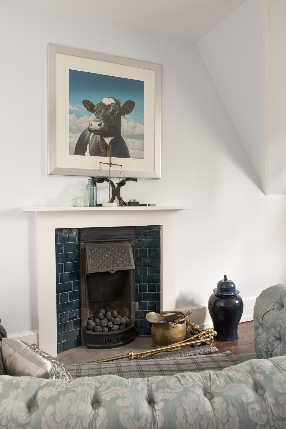 A Paul James cow painting (called Camilla) hangs above the chimneypiece