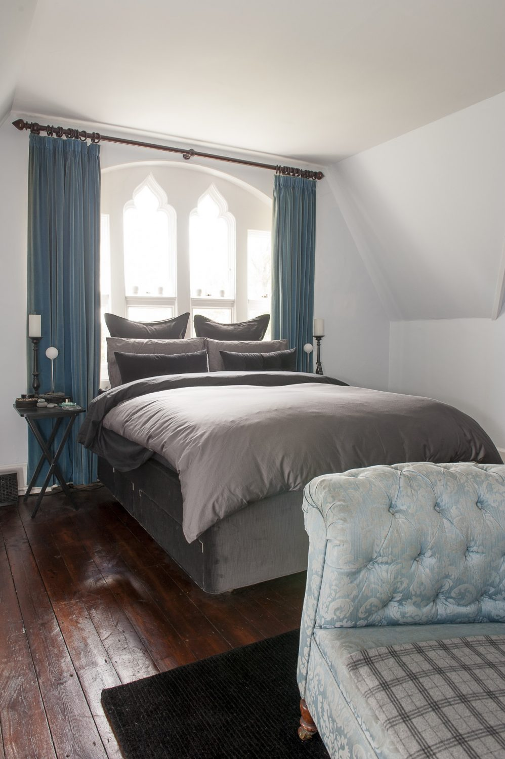 The couple's own bedroom is all greys, pale blues and turquoise warmed by glowing polished oak floorboards