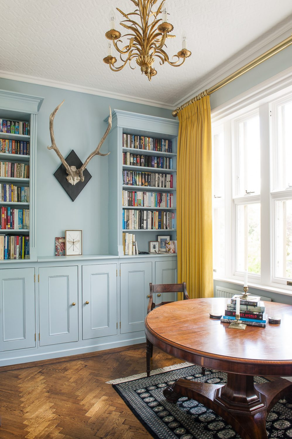 The 1840s Victorian circular table is attended by Regency chairs Dan had reupholstered in black damask. On the wall is a set of reindeer antlers