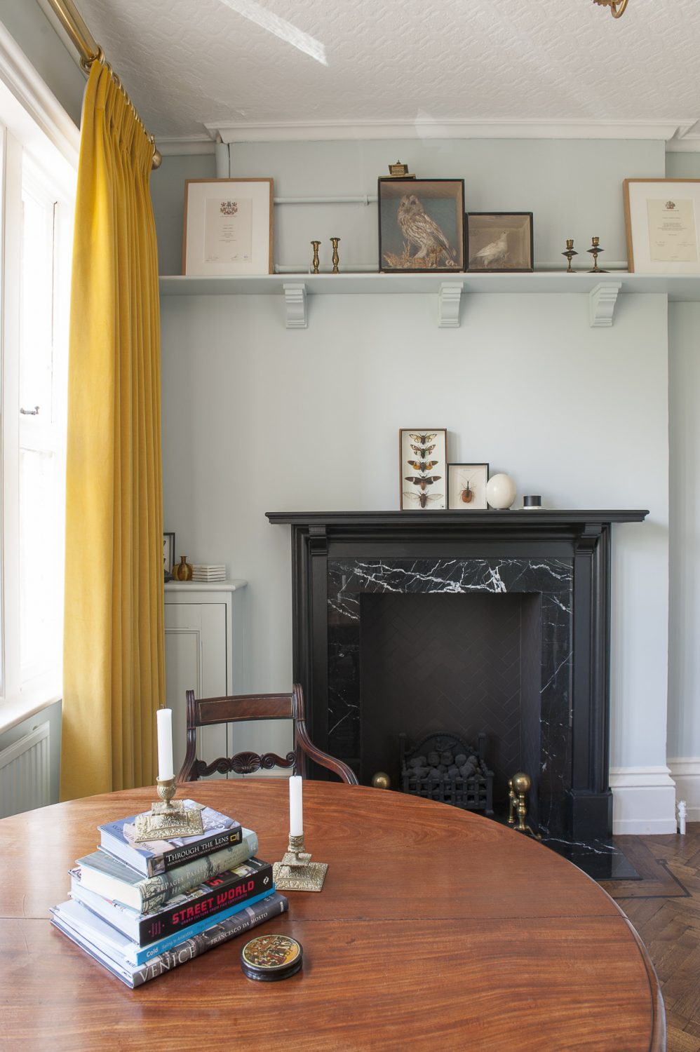 """above the chimneypiece a case of butterflies and a stuffed owl. """"Chris calls this my dead and dusty room,"""" observes Dan"""