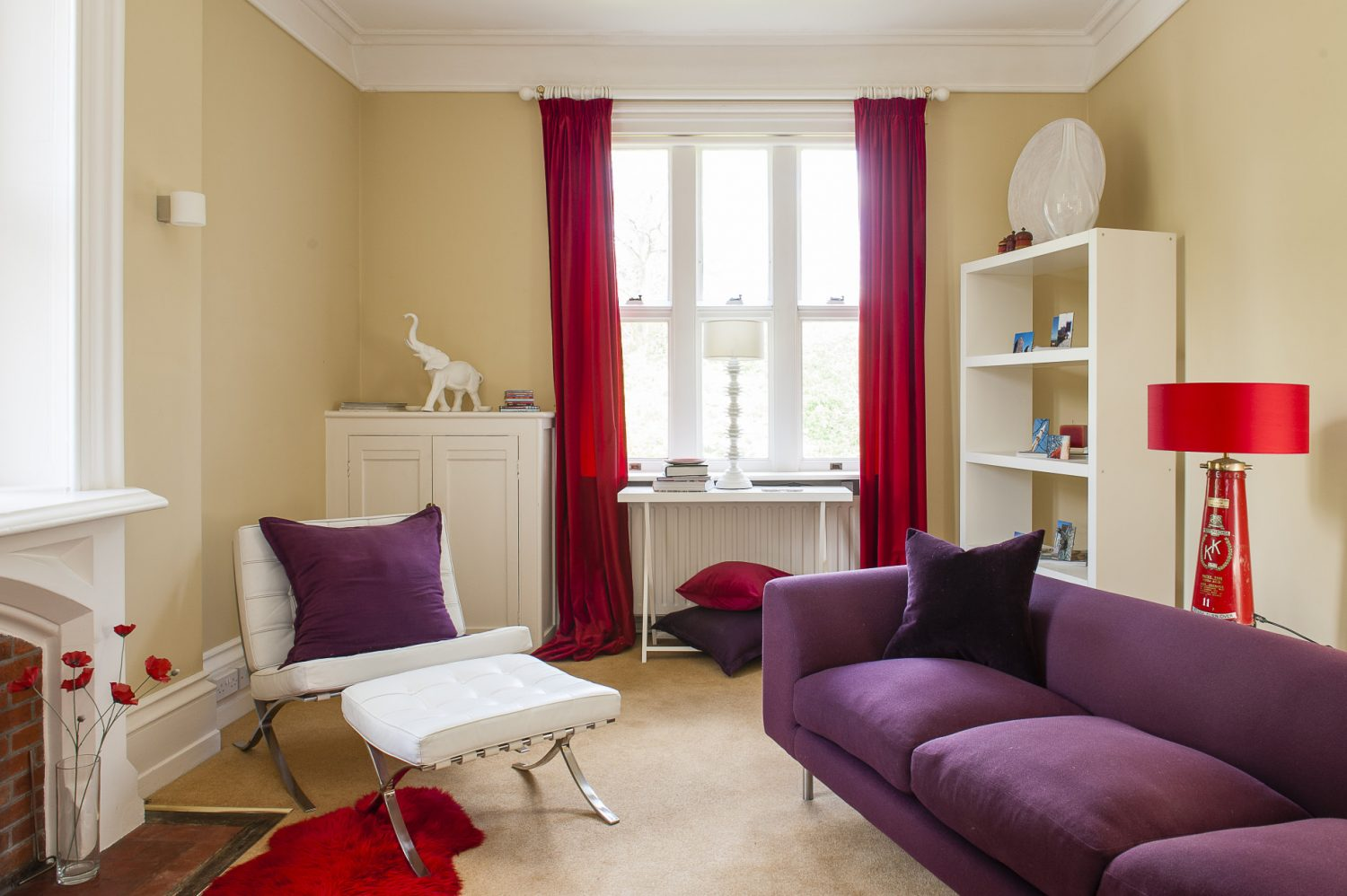 The TV room has a light mid-century touch. A comfortable purple sofa and red rug, curtains and a wonderful side lamp Chris has made from an antique fire extinguisher complete the period picture