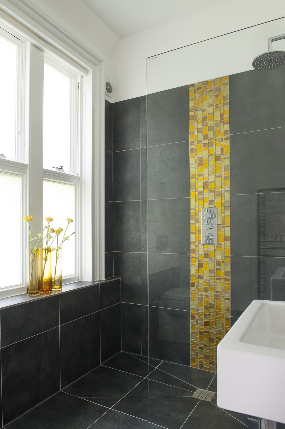 The downstairs wet room with panel of Venetian glass tiles