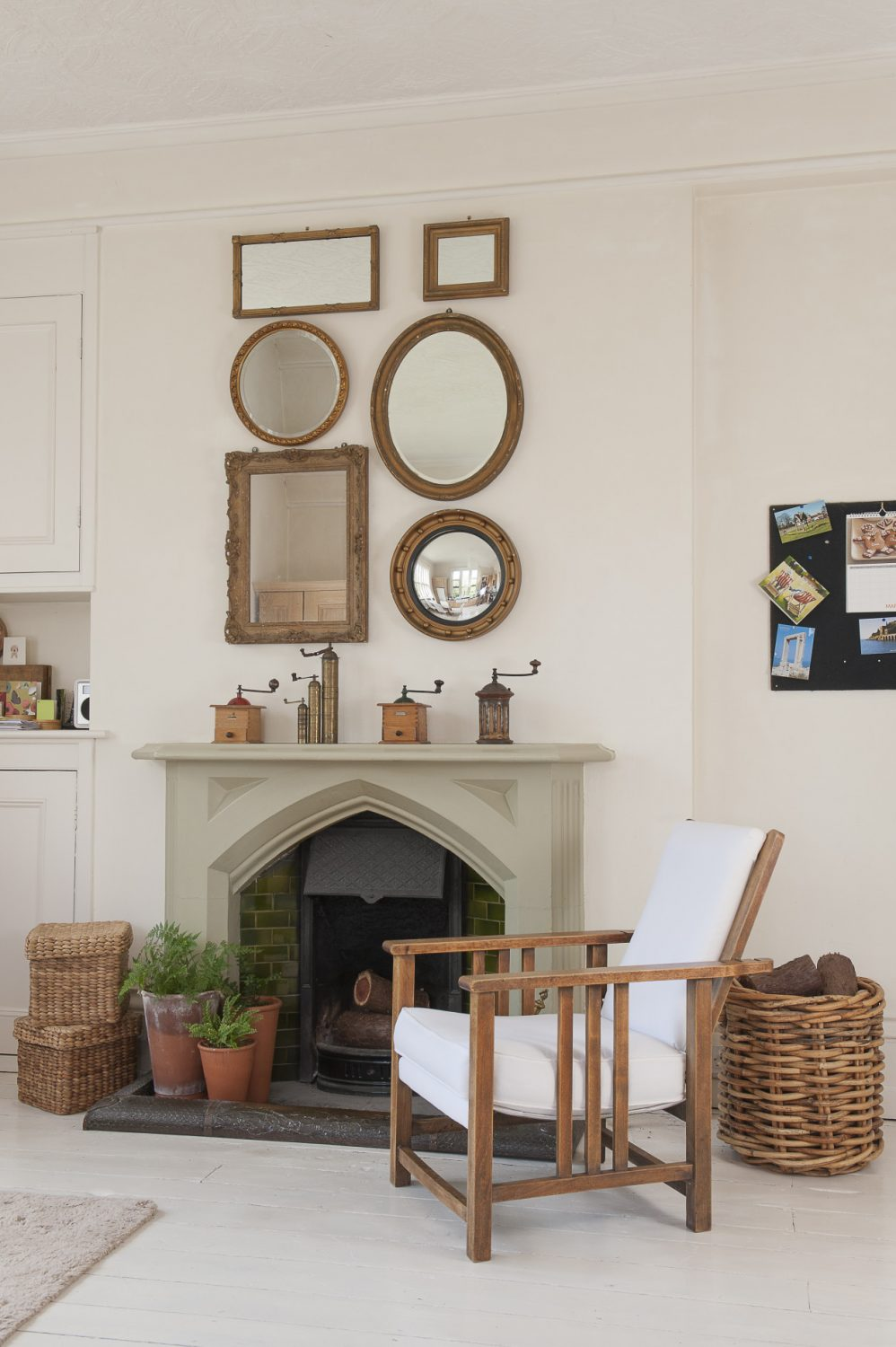 Beside the fireplace lazes a warm wood and white armchair which Dan restored himself and above it a collection of favourite gilt mirrors and antique coffee grinders