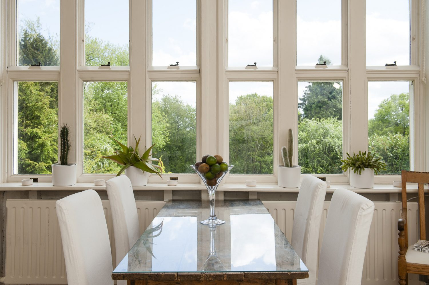 The original master bedroom is now the kitchen/breakfast room. The simple pine table has been elegantly upgraded by giving it a glass top and surrounding it with chic white Ikea chairs