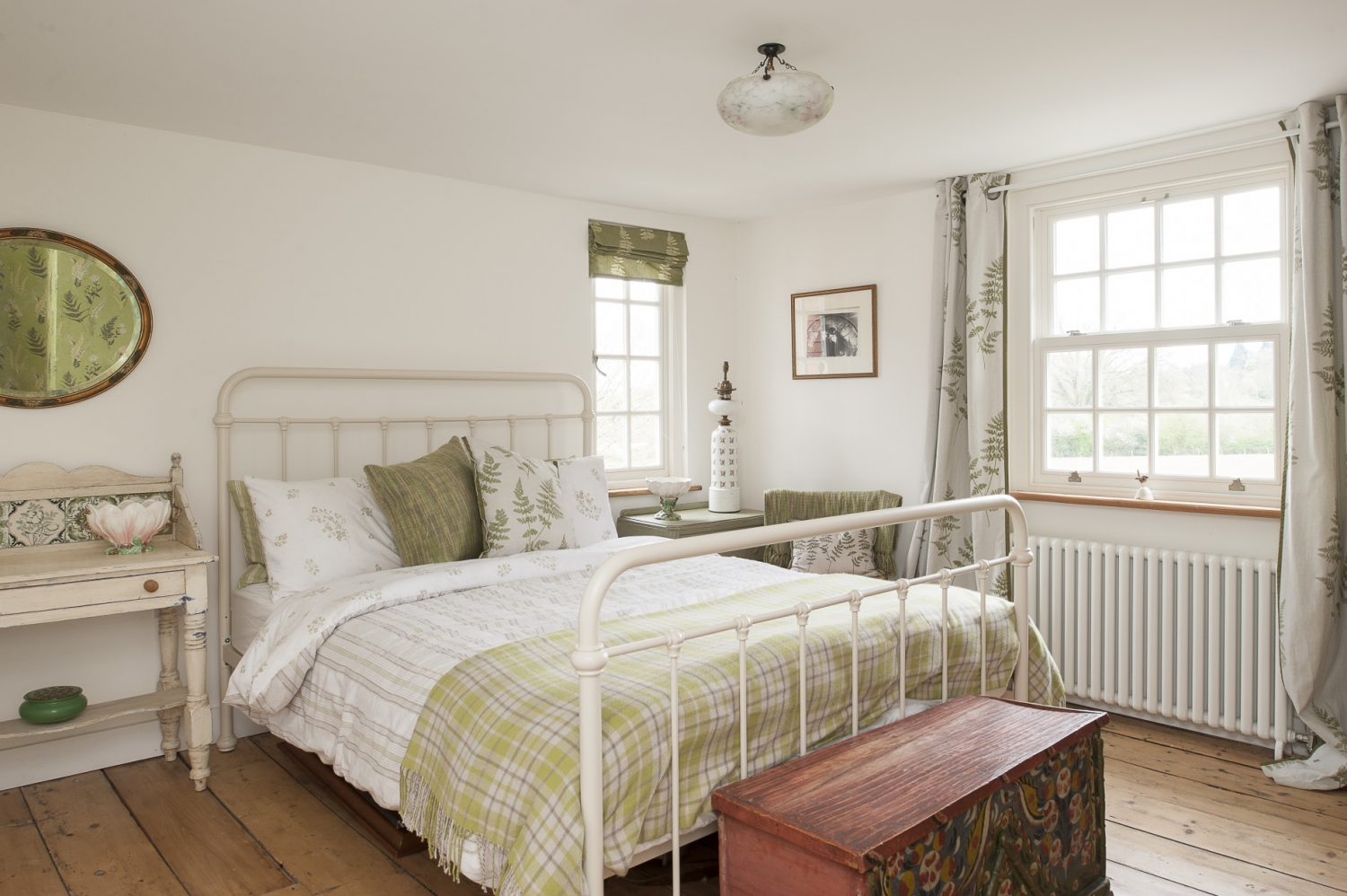 A spacious spare room is decorated in a relaxing combination of white and green, with a Victorian style metal bedstead as the focal point