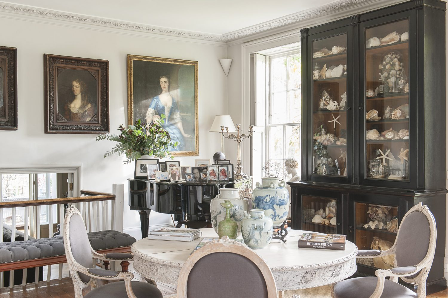 The dining area with beautiful artwork and a cabinet full of collector's items.