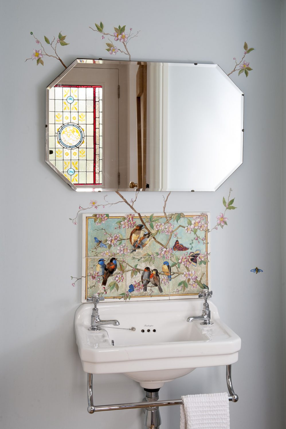 The cloakroom, just off the hall, is painted in Little Greene's 'Delicate Blue'. The tiles above are Victorian, while the murals painted around them are by Lucinda Bothwell, a local artist