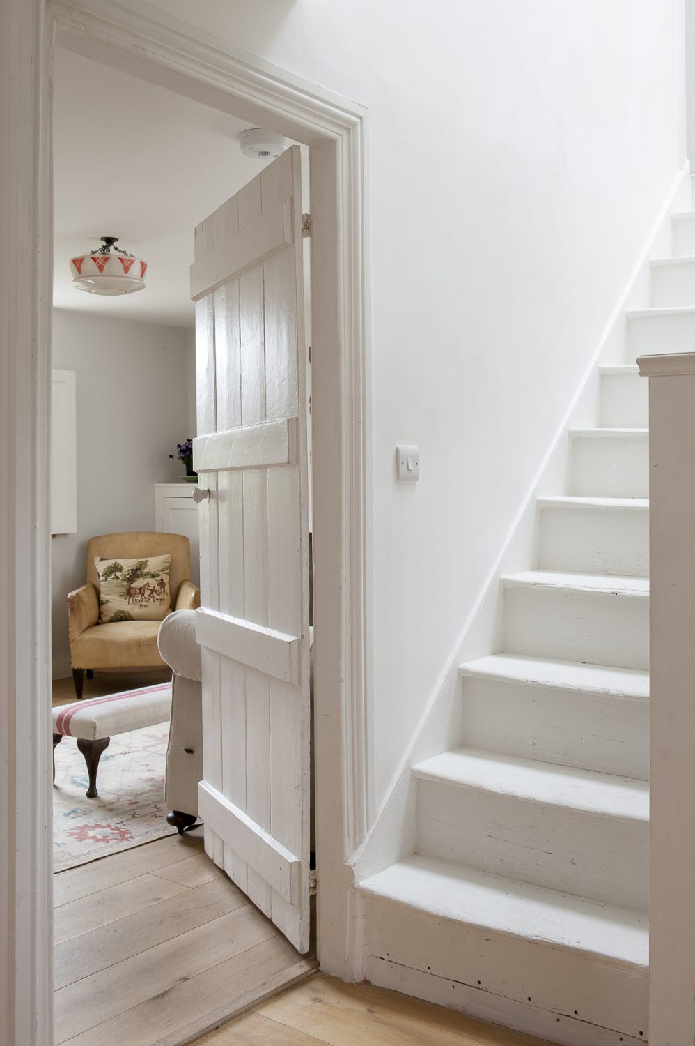 Shades of white and grey in the snug and stairwell reflect natural light