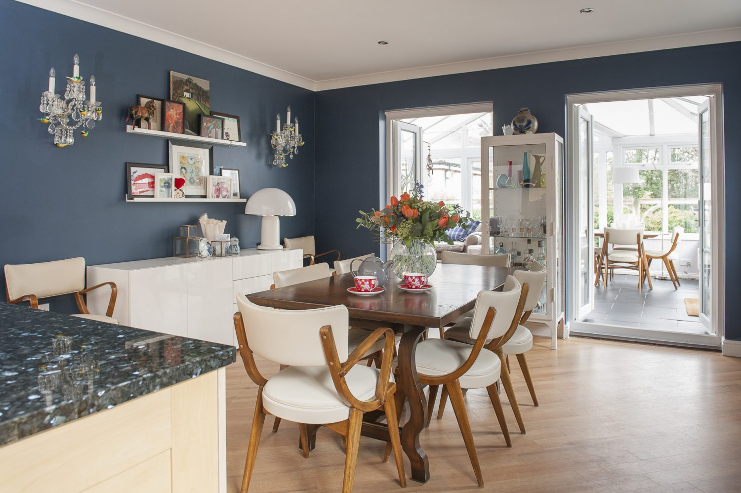 The open plan kitchen and dining room is painted a rich, deep blue