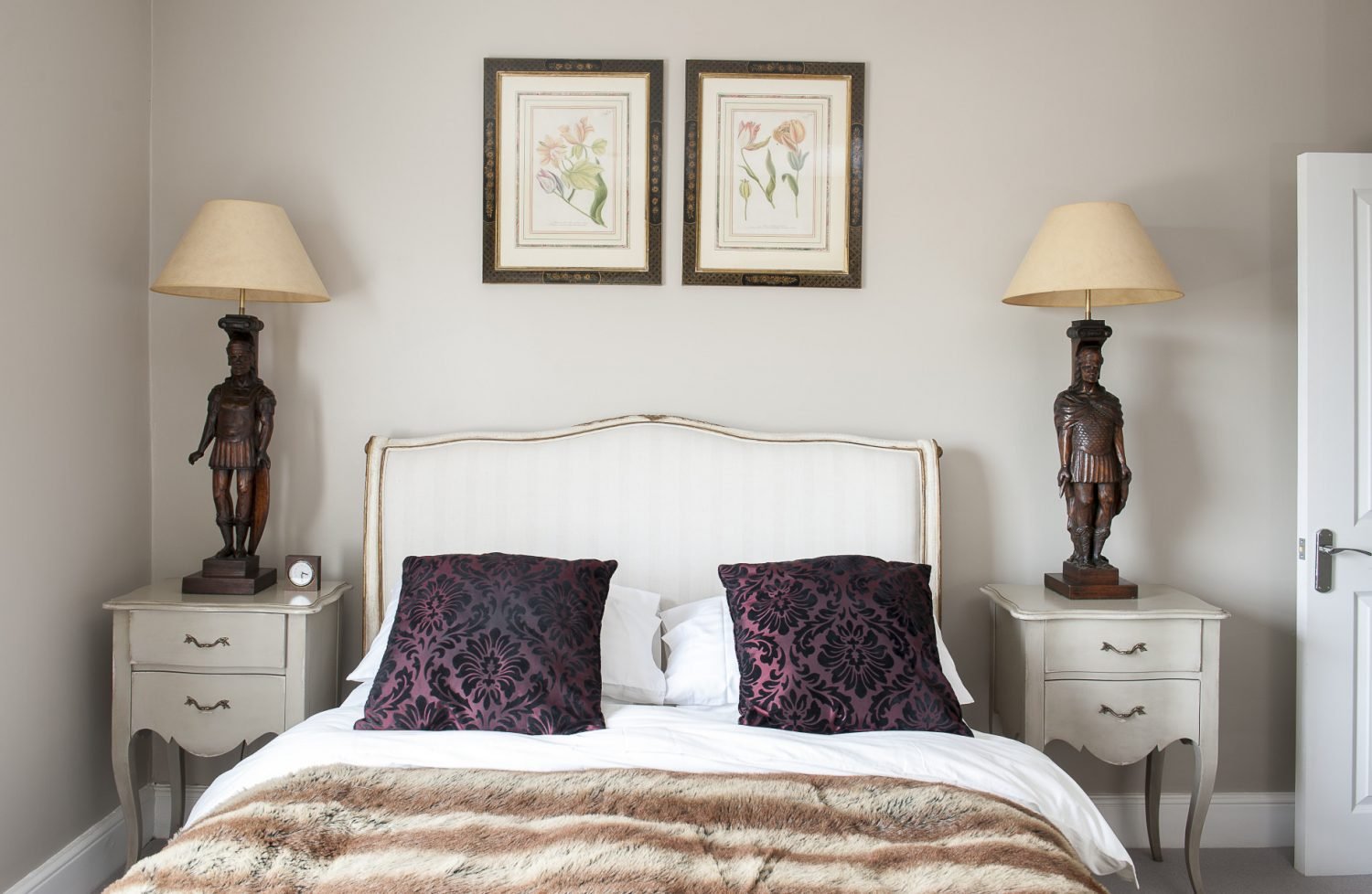 An upholstered bed from Coach House is flanked by two bedside lamps made from carved figures from a Belgian fire surround