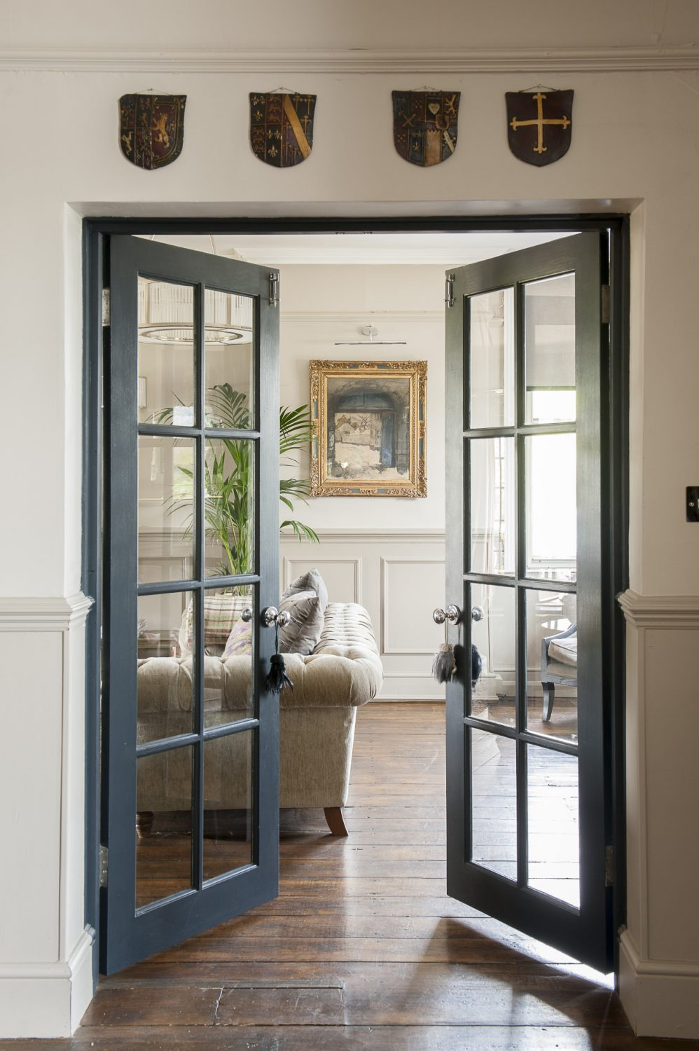 Glass doors between the hall and drawing room allow natural light to flood between the rooms at all times of day