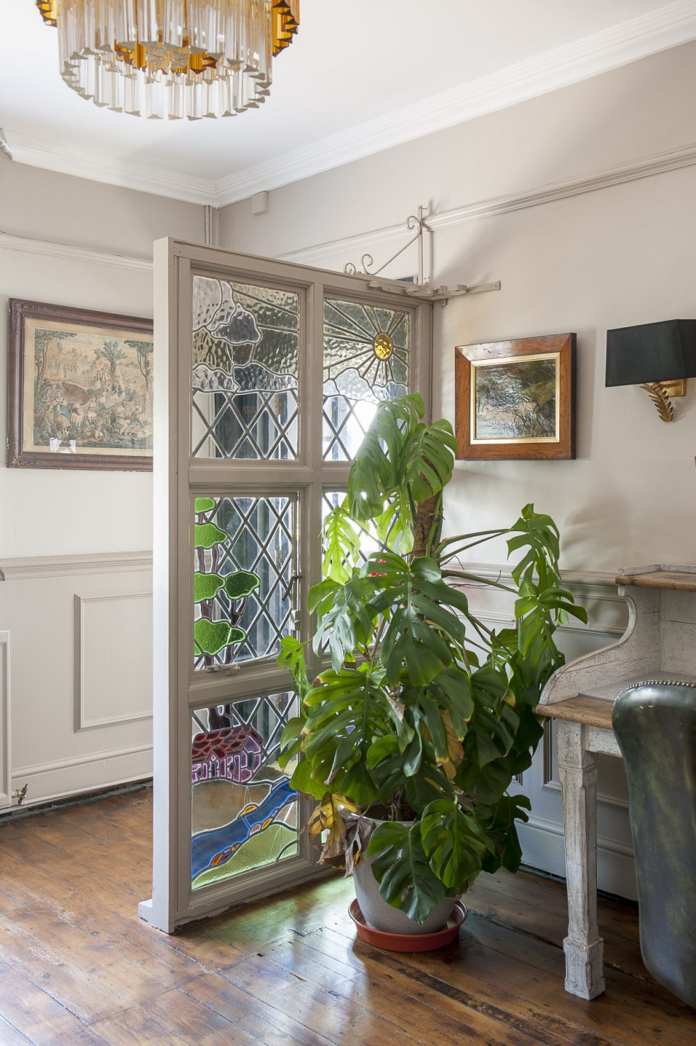 A decorative glass panel disguises the door to the downstairs loo and utility room