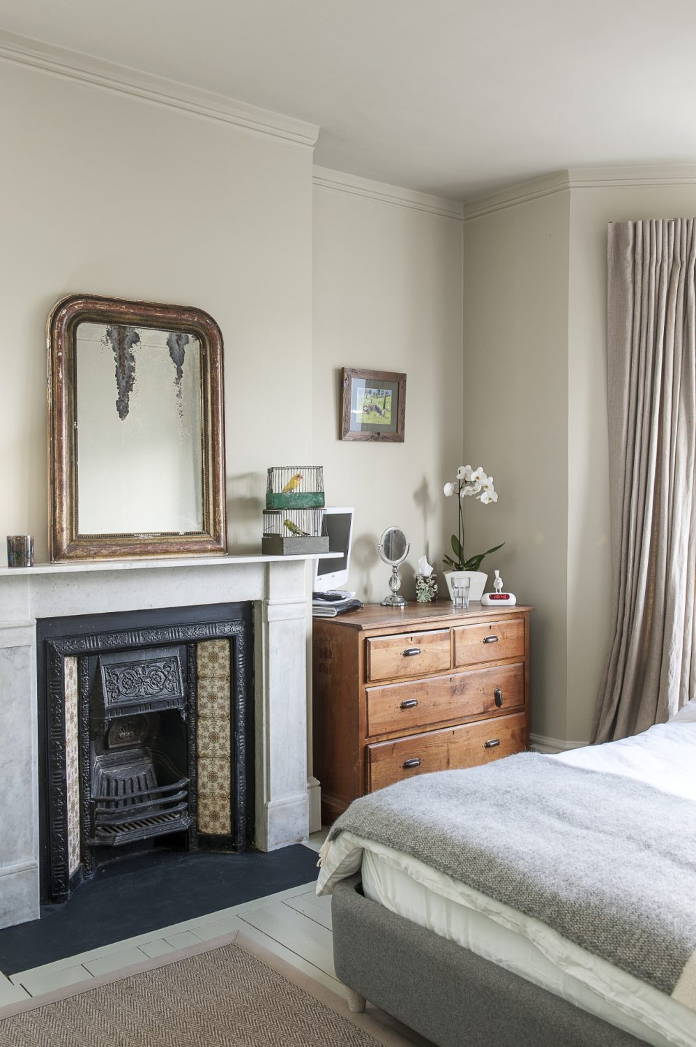 A mirror sits above the fireplace in the master bedroom