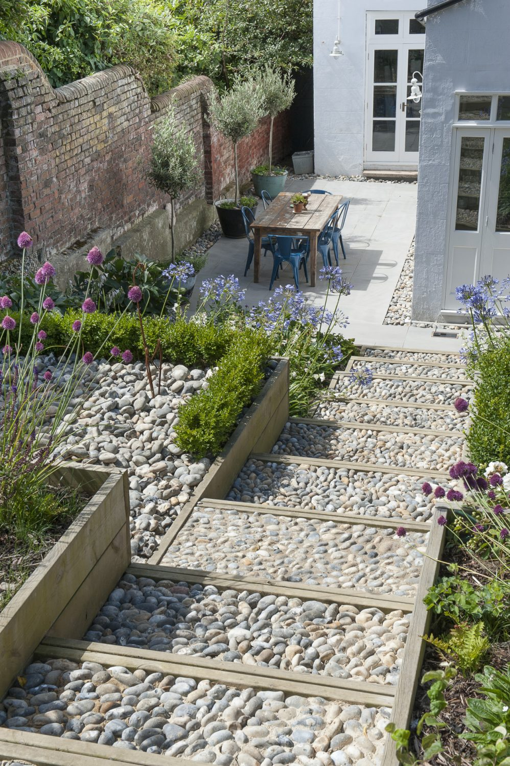 Putting her love of Gardener's World to good use Annette has created a garden using a refined and careful palette of colours. It's brimming with seasonal colour, offset by an effective combination of pebbles, wood and Indian sandstone and packed with an exuberant planting of agapanthus, allium sphaerocephalon and campanula