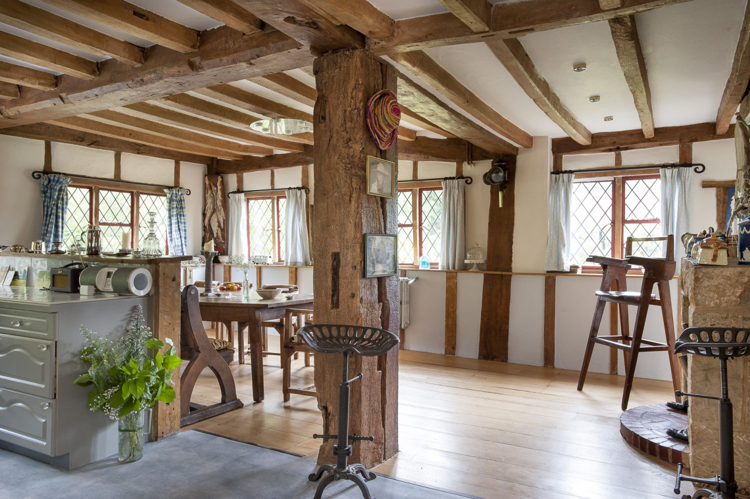 Leading from the hall – which is the heart of the house – is the traditional farmhouse kitchen, the original and oldest part of the house. Enclosed with massive honey coloured timbers and diamond leaded windows to three sides, this expansive open plan room combines the light and cheerful breakfast / dining area with the generously sized kitchen