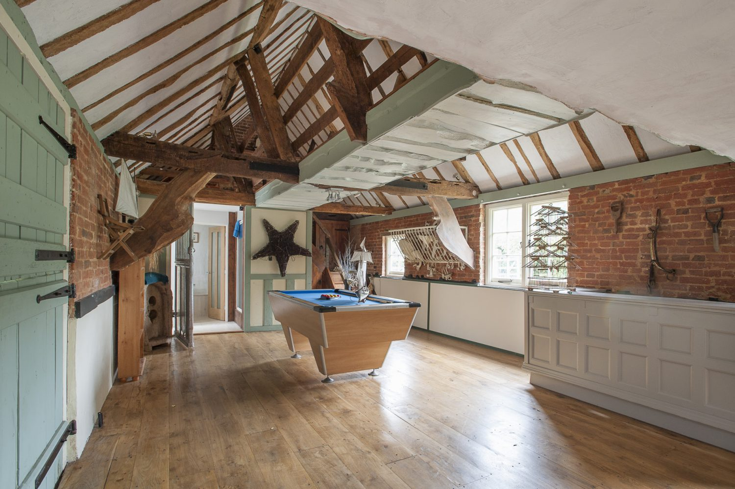 An old farm building that was once a dairy and stable has been sensitively restored to create additional living space, with many of the original features remaining like the doors and old iron stall dividers