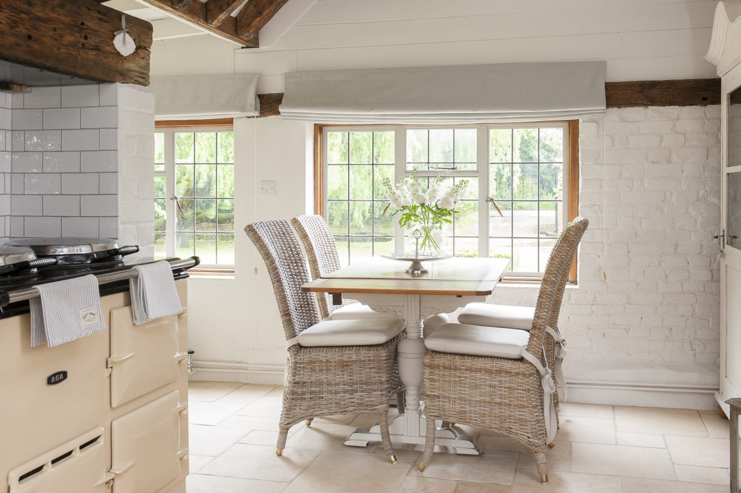 The kitchen table once belonged to Tara's aunt Colleen and was about to be thrown out and put on the bonfire but Tara saved it. She decided to leave the top as natural wood and white-distress the legs. The kitchen chairs are Lloyd Loom by Neptune and are stocked by John Lewis