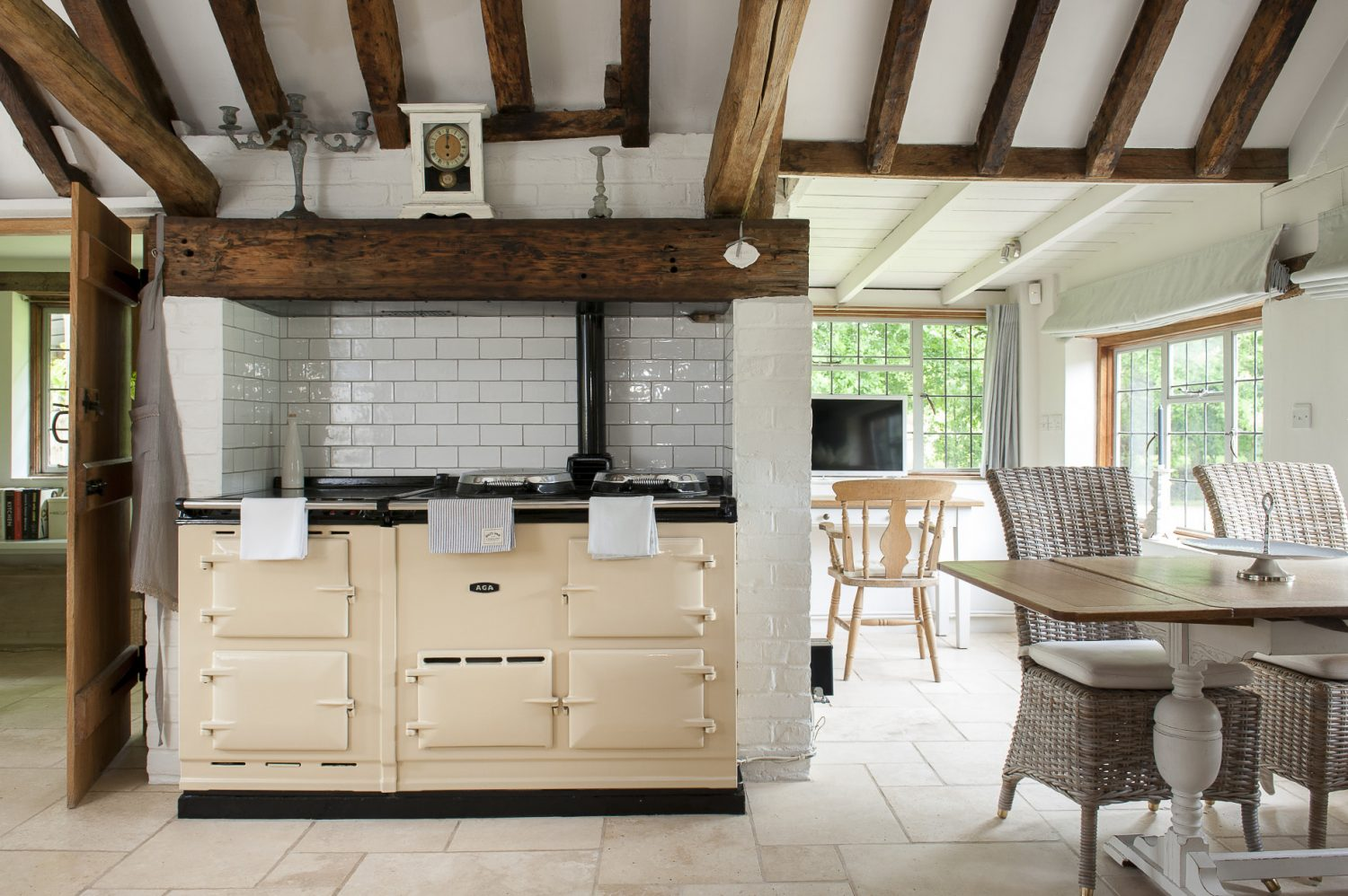 A vaulted ceiling and honey-coloured beams above the comforting cream Aga help to make the room feel light and airy. An old clock on the bressumer above the Aga belonged to Mark's parents and was once natural wood. It was given a distressed white finish by Tara