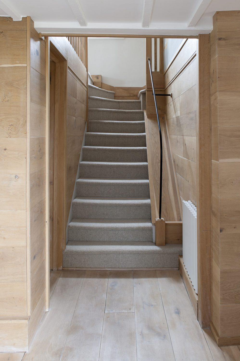 The understated, wood-lined stairway, with bespoke handrail designed by Andrew, gives a taste of the chalet style upstairs