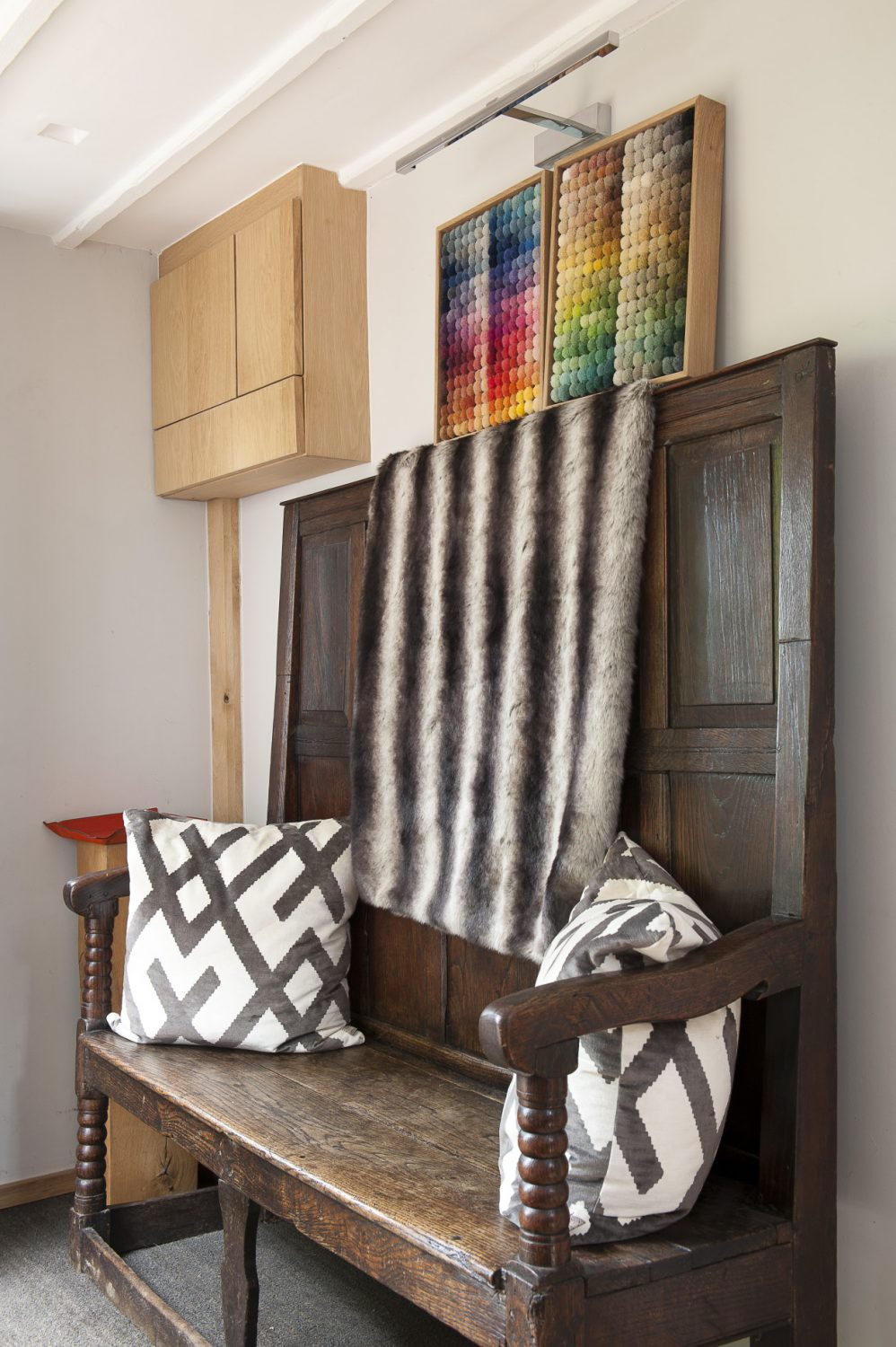 An antique settle in the downstairs hallway contrasts with a contemporary faux-fur throw, geometric-patterned cushions and colour fabric 'samplers'