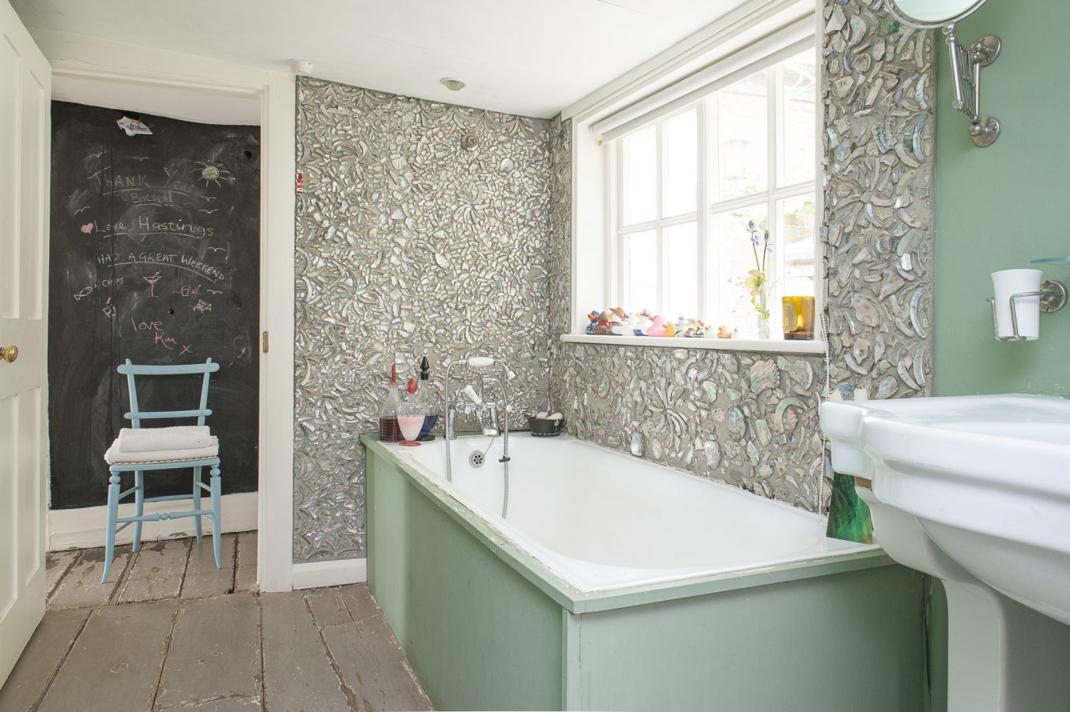 Two walls of the bathroom were mosaiced by Lionel in an intricate pattern made from crushed shells that were sourced from South Africa by a friend. Outside the bathroom, a warm thank you message has been chalked onto the blackboard wall by a friend
