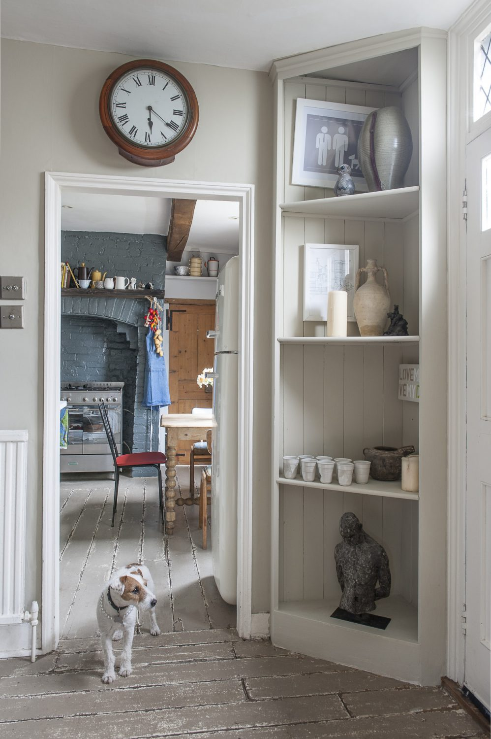 Lucy stands guard by the front door. Artist Bill Barratt has treated the floorboards with two layers of flat oil paint, in different shades, to give a distressed finish